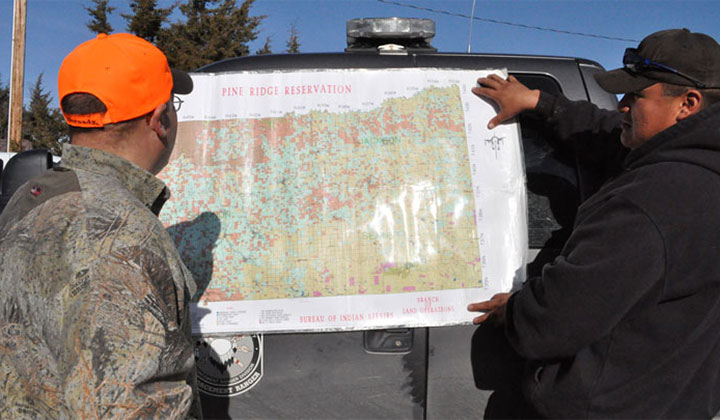 hunter and guide scan a map of the Pine Ridge Indian Reservation