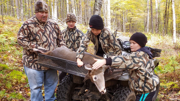a father and his sons gather around a deer they have hunted