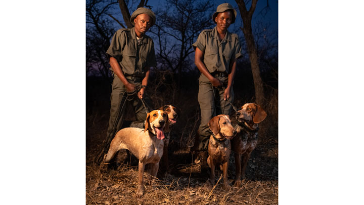 dog handlers pose with their scent hounds